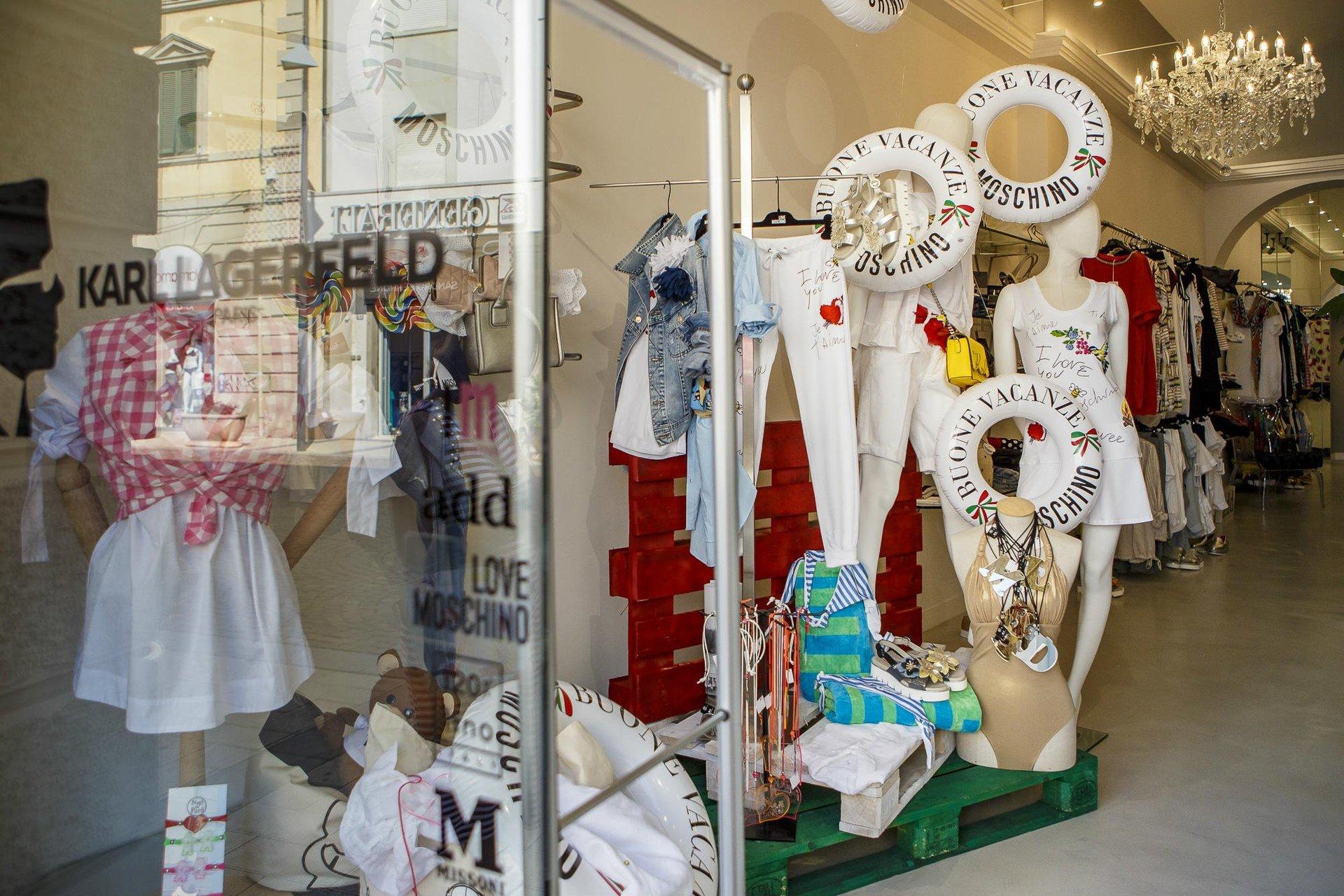 dei manichini con abbigliamento estivo e una vetrata con scritto Karl Lagerfeld