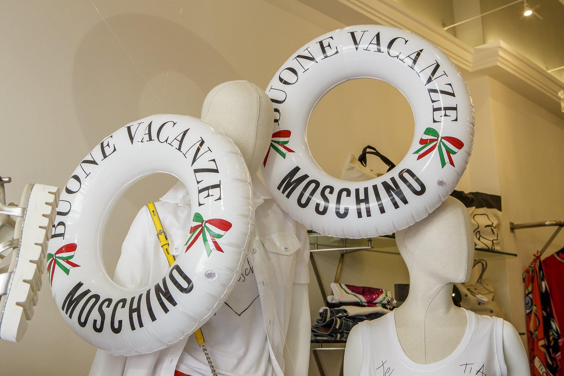 due manichini con abiti di color bianco e due salvagenti con scritto Buone Vacanze Moschino