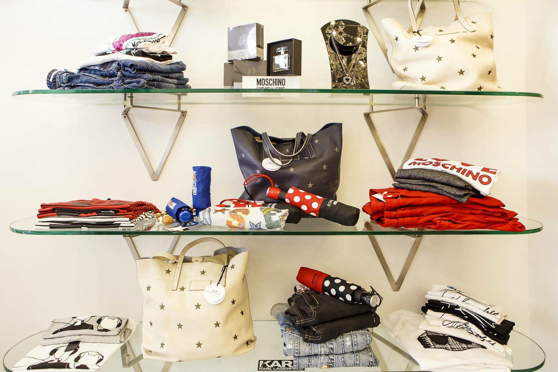 delle mensole di vetro con le borse , delle magliette e altro della marca Moschino