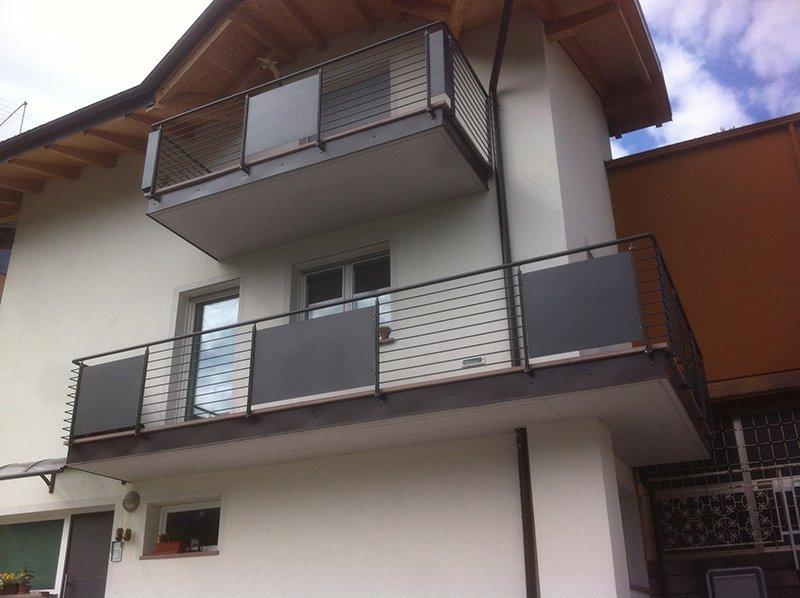 una casa con facciata bianca,tetto in legno e due balconi con le ringhiere in ferro battuto