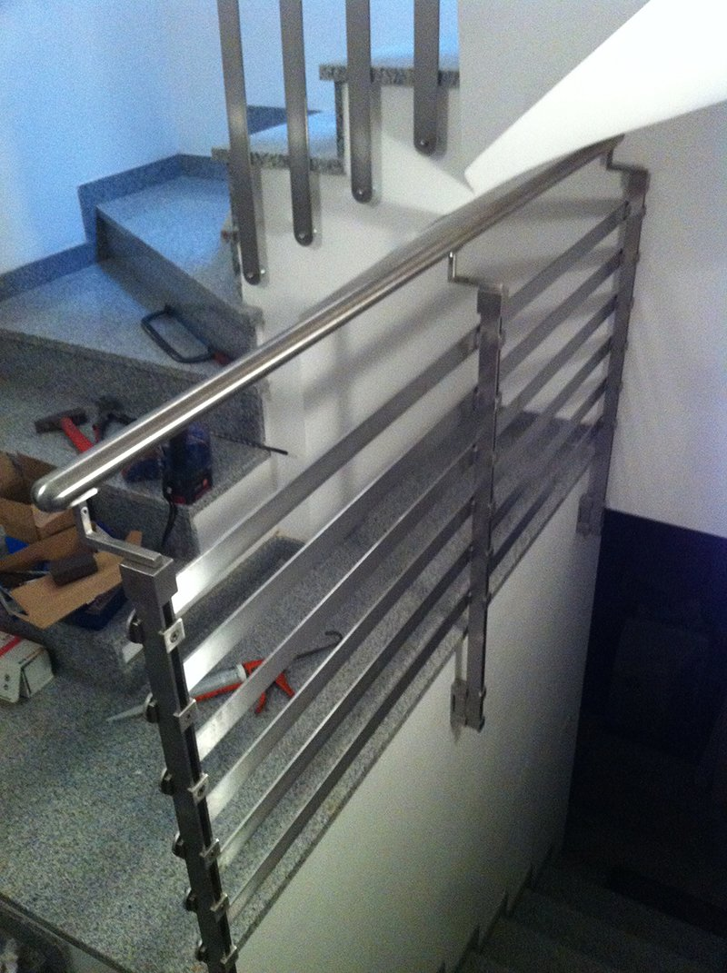 il corrimano in ferro di una scala e accanto una cassetta con degli attrezzi