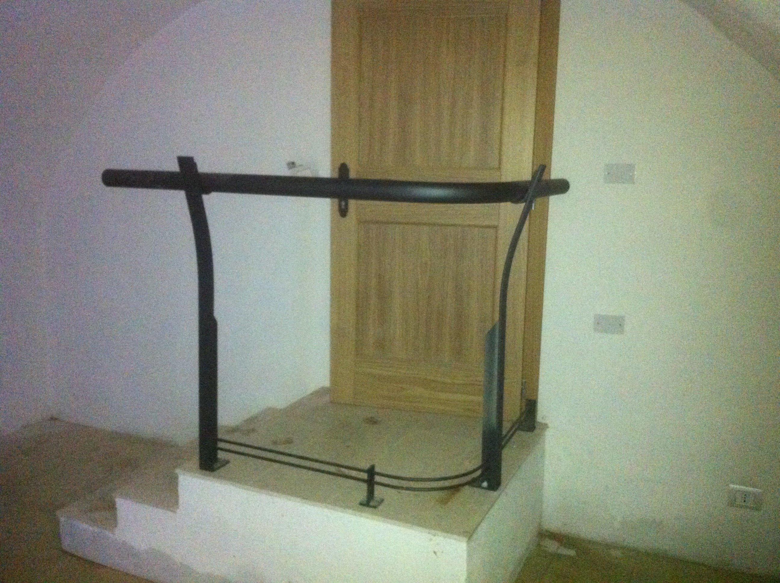 tre gradini, un corrimano in ferro nero e una porta in legno