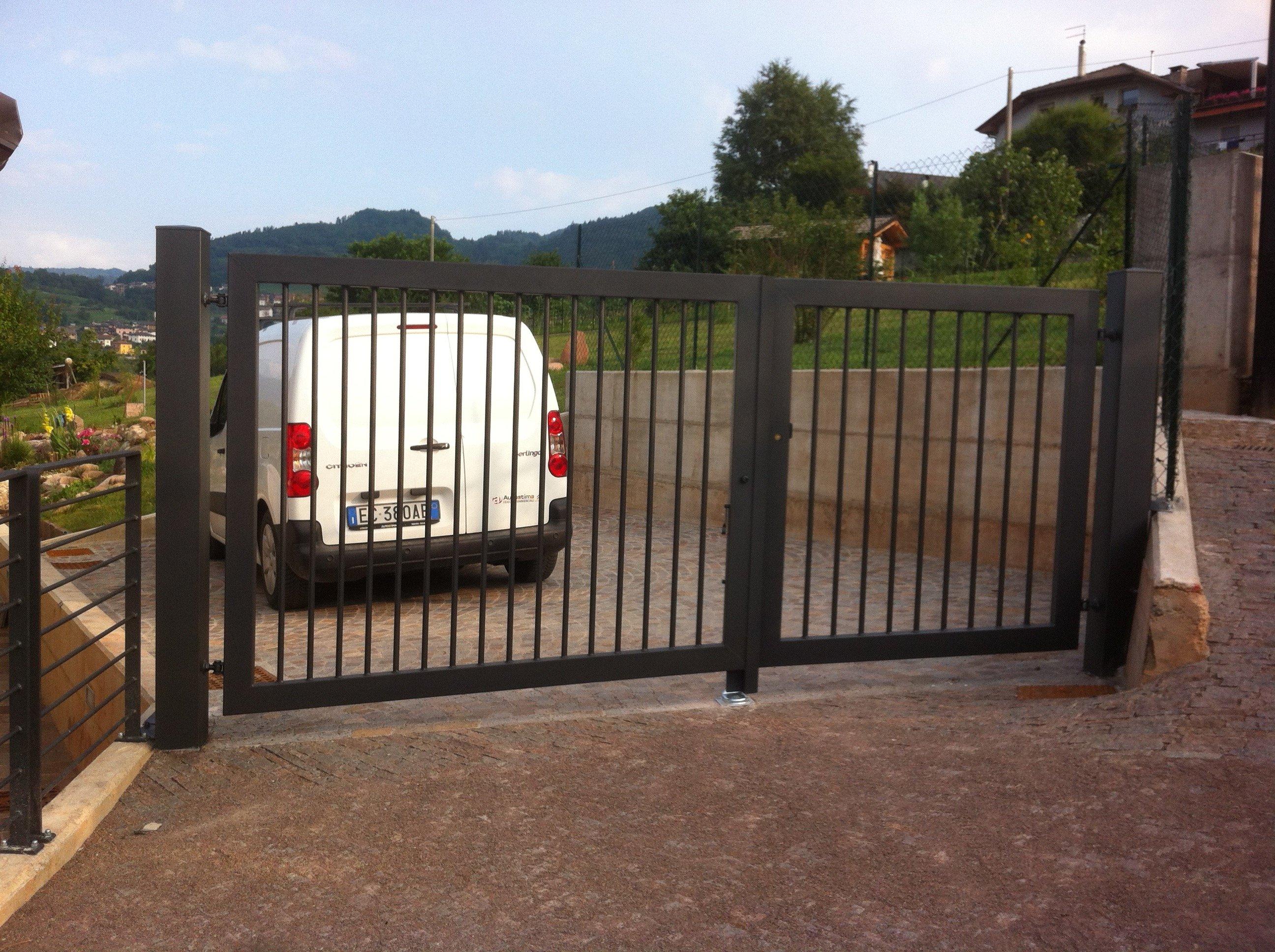 un cancello in ferro e fuori un furgone bianco parcheggiato