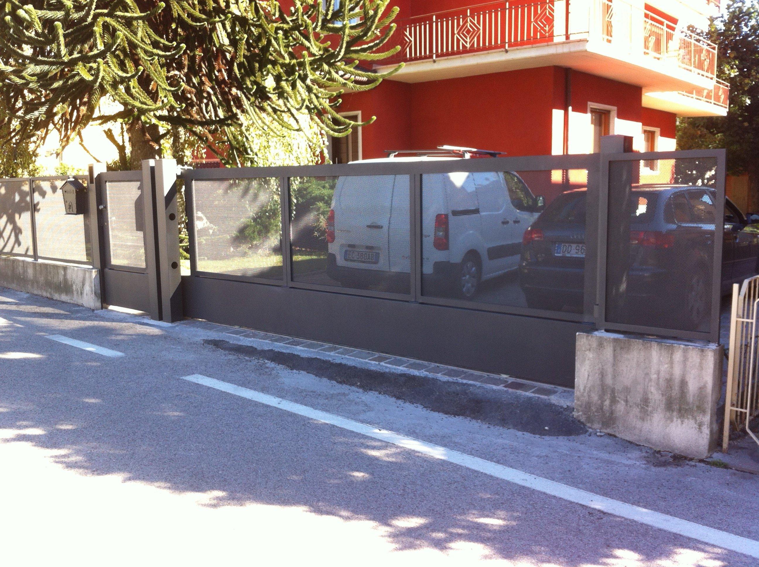 un cancello in ferro e vetro all'esterno di un condominio di color rosso e dentro dei veicoli parcheggiati