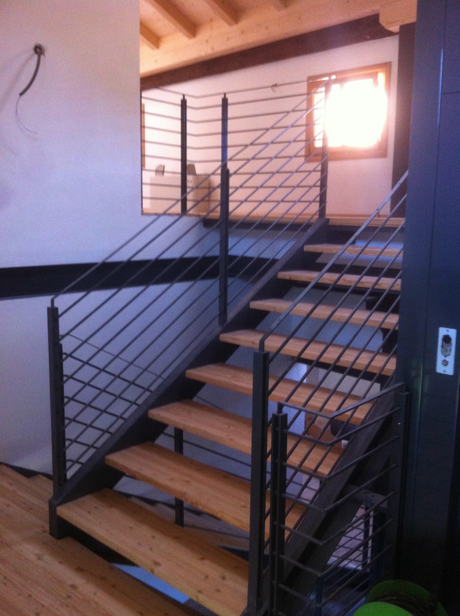 dei gradini in legno di una scala e su entrambi i lati dei corrimano in ferro