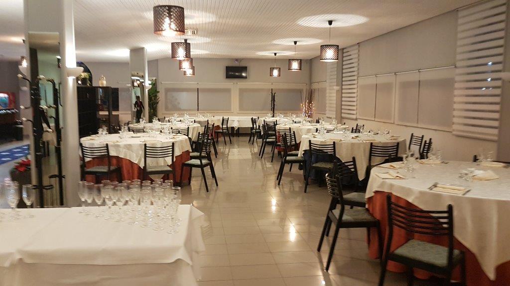 vista interna del ristorante con tavoli apparecchiati e lampadine in soffitto