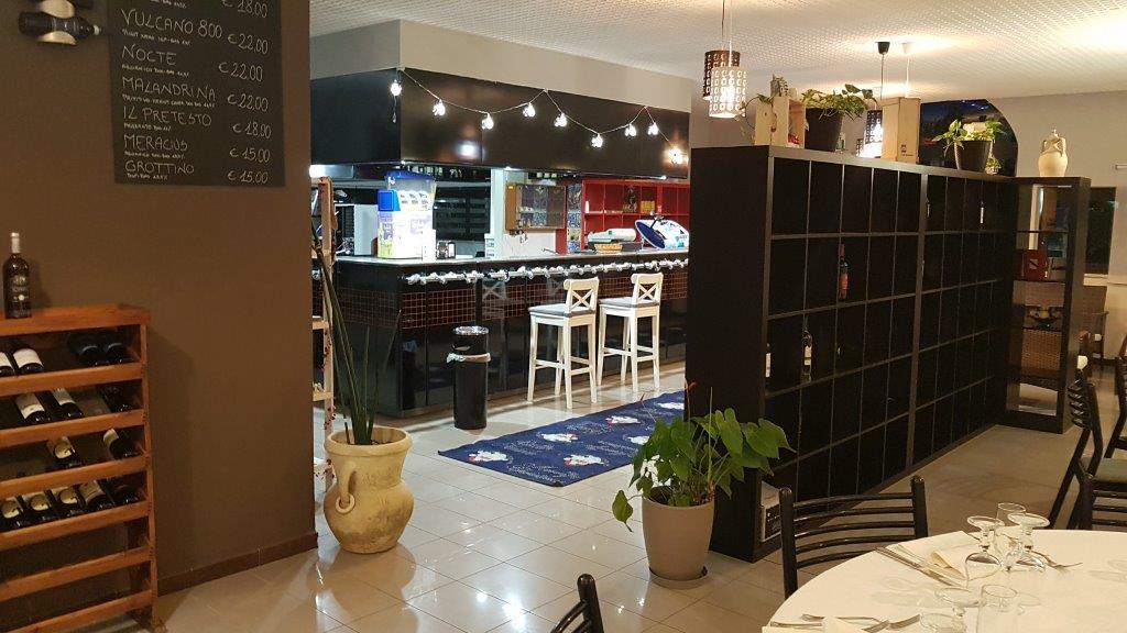 vista laterale di un bancone di cucina moderna con scaffali in legno e arredamenti