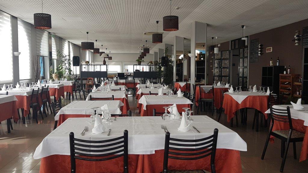 vista frontale del ristorante con tavoli apparecchiati, sedie e lampadine in soffitto