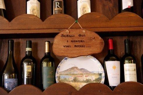 scaffale di vino con scritto scegli qui i nostri vini rossi