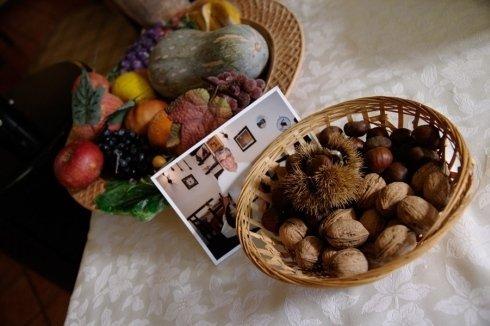 due cestini di frutte e noci e una foto di uomo