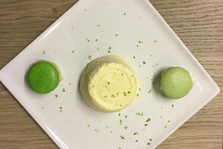 due macarons francesi colorati e al centro un dessert alla panna