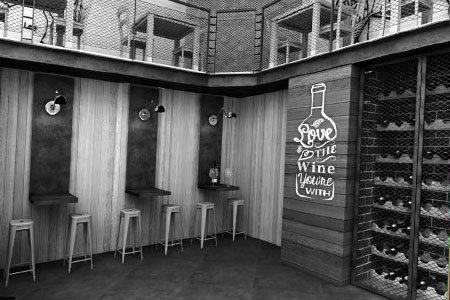 una foto in bianco e nero raffigurante sulla destra uno scaffale con dei vini e una bottiglia disegnata con delle scritte
