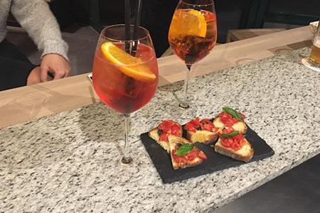 un tagliere con delle bruschette e due bicchieri con dei cocktail
