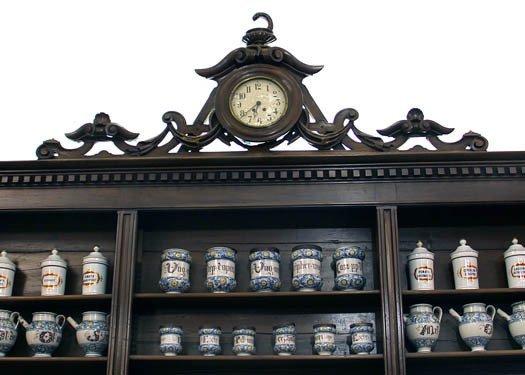 Antico scaffale con vecchi recipienti di erbe e orologio centrale