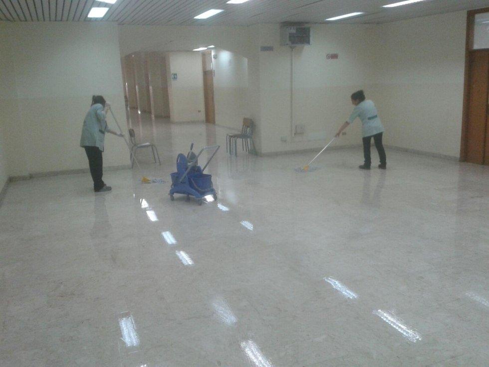delle donne di pulire il pavimento in marmo