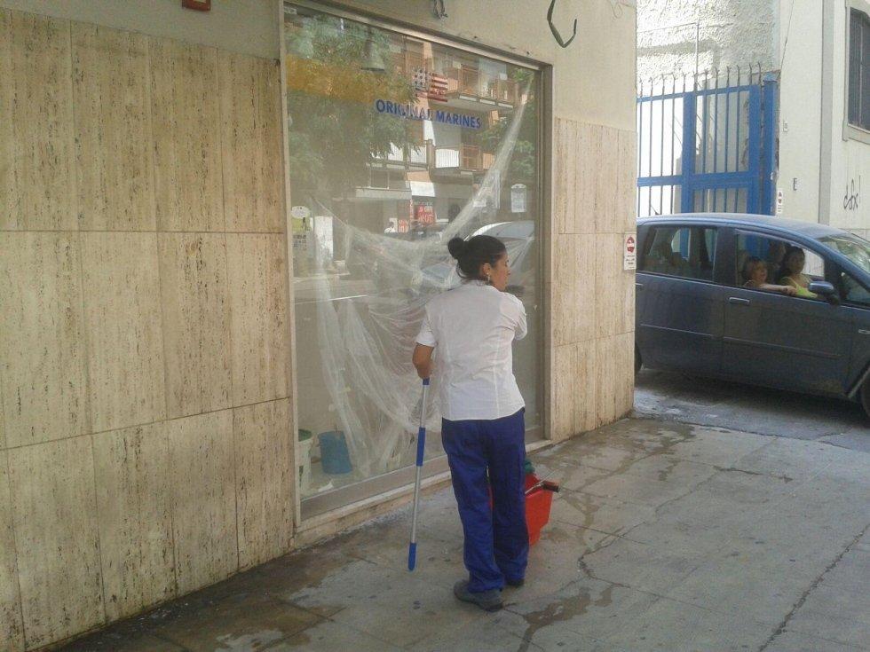 donna delle pulizie del negozio fuori della finestra