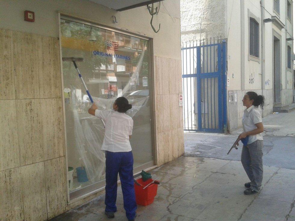 due donne delle pulizie del negozio fuori della finestra