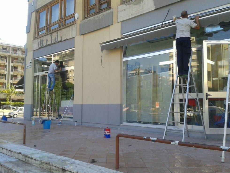 la pulizia del tetto e la finestra negozio due uomini