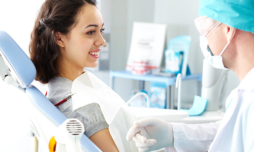 Young female patient looking at dentist while he describing the process of dental treatment