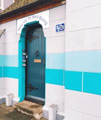 blue door set in a mediterranean white wall
