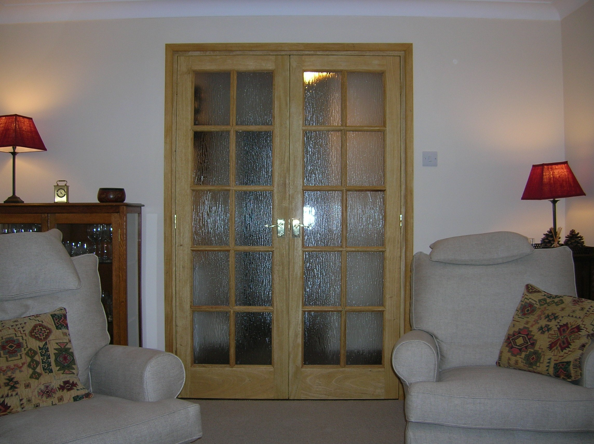 glazed double lounge doors with two armchairs and table lamps