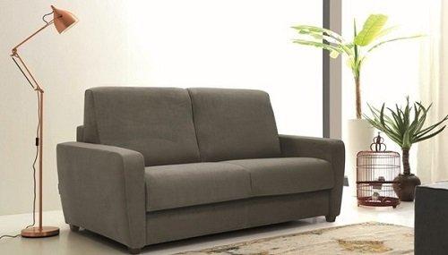un divano di color grigio e accanto una lampada da terra