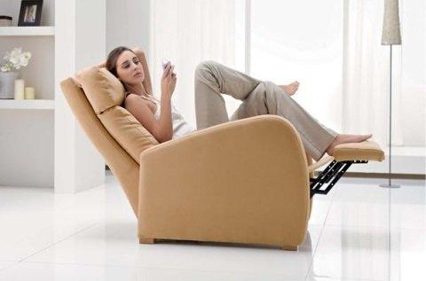 ragazza seduta su una poltrona recliner di color beige