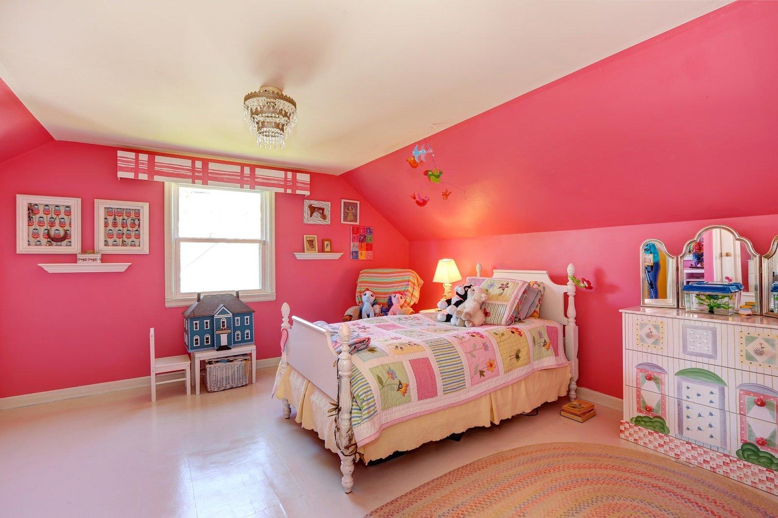 una camera con un letto singolo e dei muri di color rosa