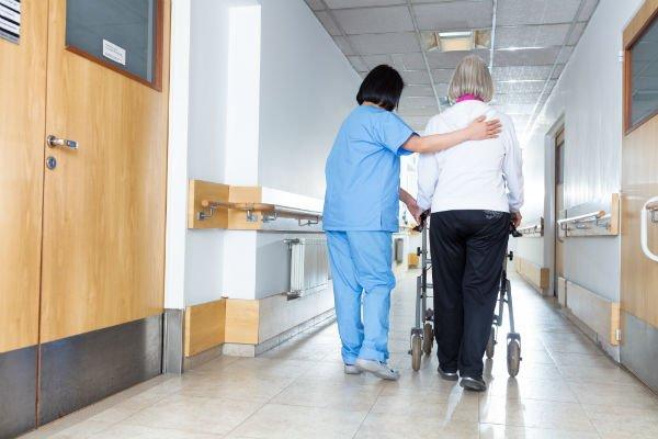 un'infermiera che accompagna una signora anziana
