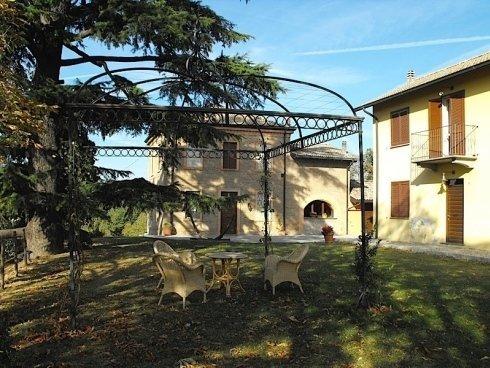 Il giardino con la pergola, i mobili e al fondo la tenuta