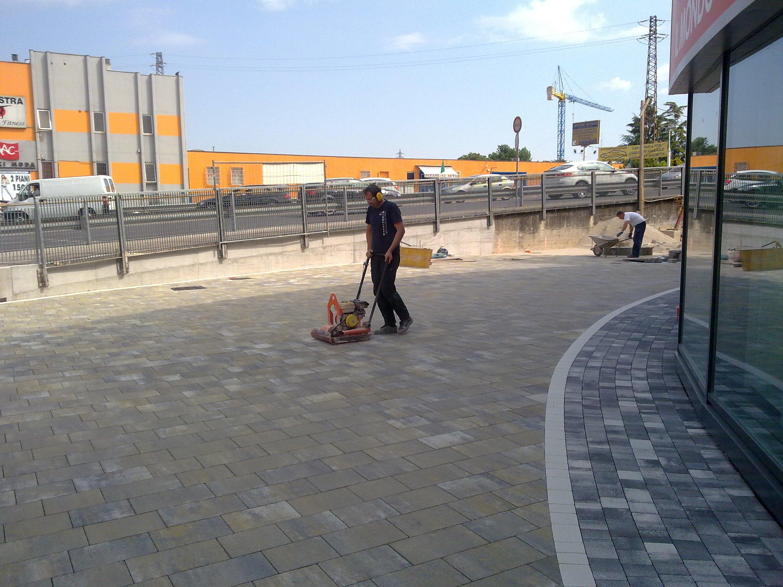 un uomo mentre lavora la pavimentazione in pietra