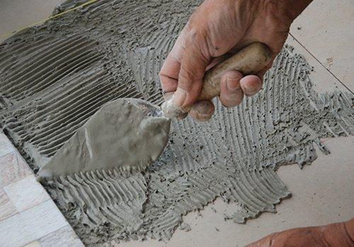 Una mano con una spatola e del cemento fresco