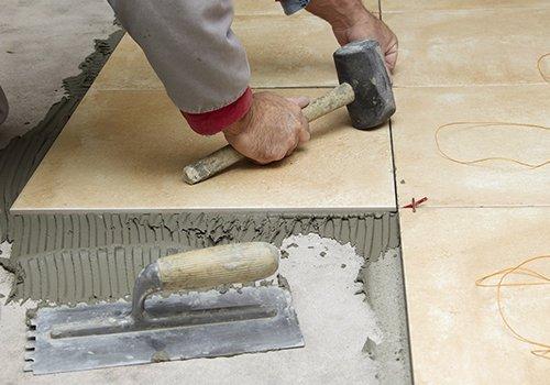 Una mano con un martello di gomma che fissa delle piastrelle sul