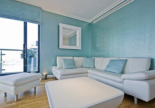 Un salotto con un divano bianco e dei pouf