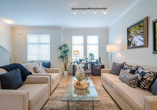 Un salotto con un tavolino di vetro al centro e dei divani beige