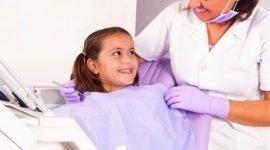 bambina seduta sulla sedia del dentista, assistente che sorride, clima disteso