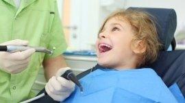 bambina che sorride, mani del dentista, strumenti dentistici