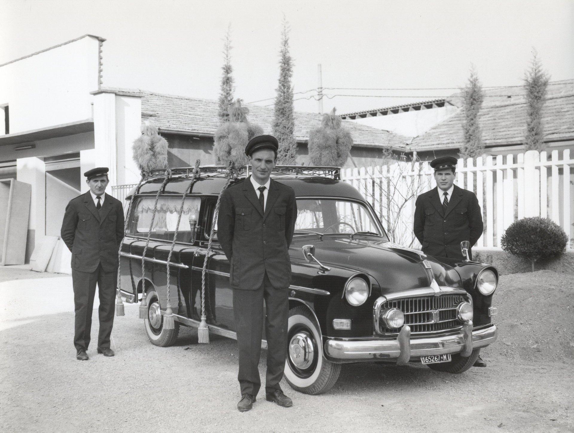 un carro funebre e accanto un furgone