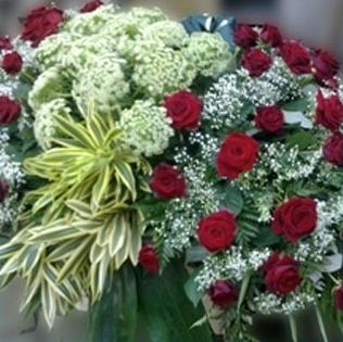 una composizione di rose rosse e fiori bianch