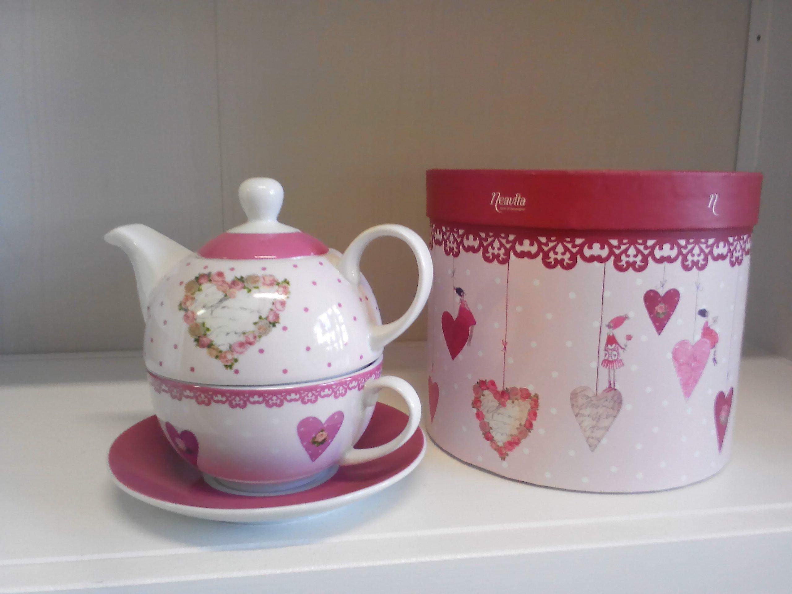 un teiera bianca  e una scatola a cuoricini rosa