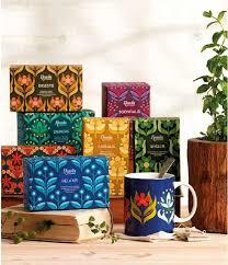 delle scatoline di cartone colorate, una tazza blu con dei disegni e un vaso con una pianta