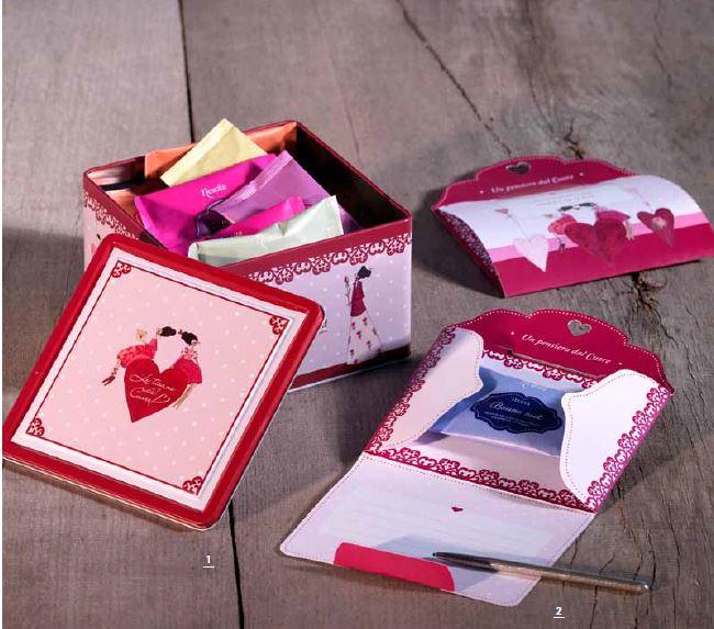 una scatola di latta aperta e affianco dei dei cartoncini bianchi e rossi a disegni e una penna