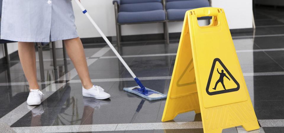 A cleaner mopping the floor with a wet floor sign nearby