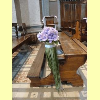 mazzo di fiori sopra una panca in chiesa