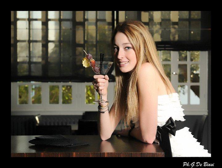 una ragazza bionda con in mano un bicchiere con un cocktail