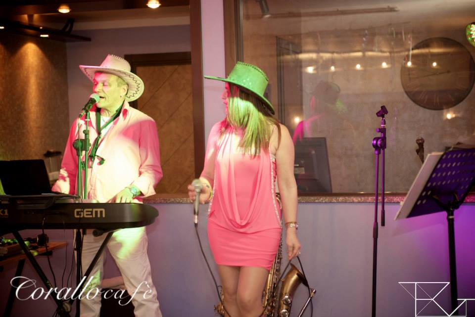 una donna con un microfono in mano e un uomo che canta e suona una tastiera