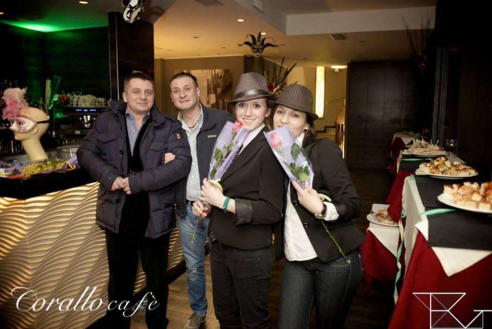 due ragazze con dei cappelli e delle rose in mano e dietro due ragazzi