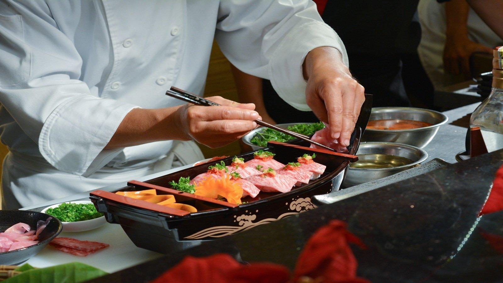 due mani di un cuoco con delle bacchette e un piatto di sushi