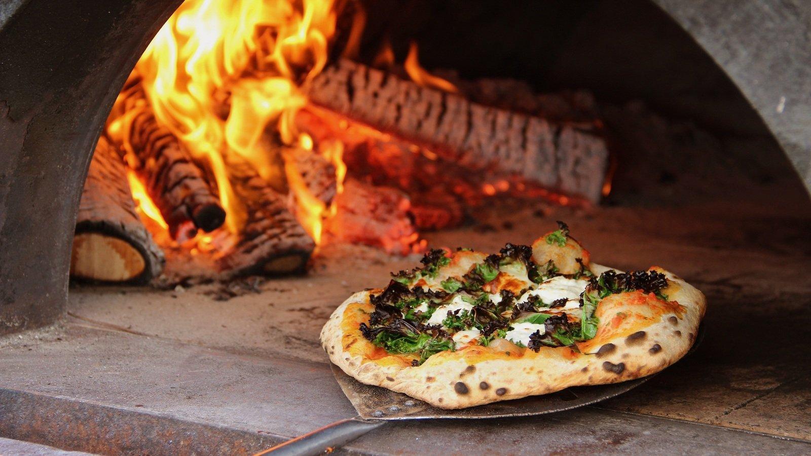 pizza che sta per essere infornata in un forno a legna