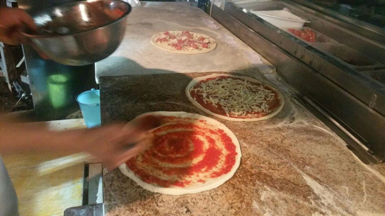 due mani di un pizzaiolo che preparano delle pizze